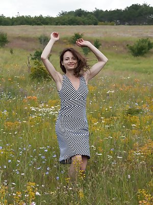 Shaya is enjoying herself in the fields and has a sexy grey dress on. She takes off her dress and panties off and relaxes on her red towel. She masturbates and fingers her hairy pussy and has fun.