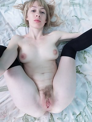Natinella enjoys her black tights whenever she wears them, and is posing by her mirror. Her black lingerie comes off and she lays in bed naked. She has a fluffy hairy pussy and a sexy body.