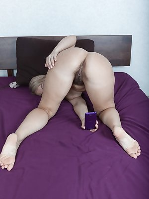 Luiza M is having fun on her phone while in bed and strips off her floral top and lingerie to get nude. She takes selfies of her naked body and then masturbates with her vibrator in bed to scream and moan.