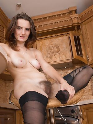 Ira stands in her new wooden kitchen, and strips naked to show off her body. Her lingerie and stockings come off, and show us her full hairy bush. She climbs on the able and fingers herself there too.