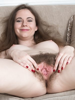 Camille is by her couch and stripping naked. The jeans and blouse come off and she shows her 34C breasts and hairy pits. Naked on the couch, she spreads her legs open and isn't shy about her hairy bush.