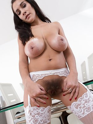The sexy Mischel Lee is in her black dress and white stockings. She takes it off and she shows off her full hairy pussy. She lays back and tugs on her pussy hair and fondles her 42DDD pair of breasts.