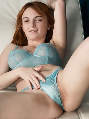 Lola Gatsby in her tight dress shows off her petite 5'2' body. Under, her blue lingerie clings her all-natural figure. Then, she crawls across her white leather chair to reveal her hairy pussy and body.