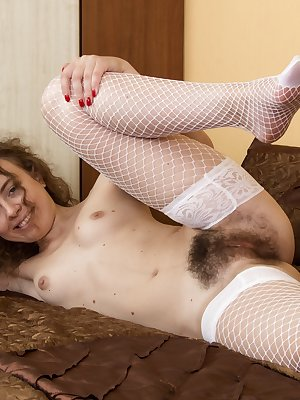 Viola R looks fetching in her floral top, white tight shorts and stockings. With an erotic flair, she strips naked and shows off her flowing hairy pussy. She is young and all-natural but with a sexy body.