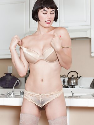 Cocco looks beautiful in the kitchen, and wears sexy stockings while showing off her ass. She strips slowly until she gets naked and starts fingering her hairy pussy. She looks amazing and super sexy.