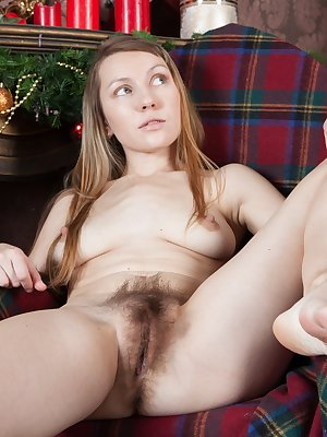 It's Christmas, and Stella is in her blue dress by the tree. She opens her gifts and then slowly strips naked by the tree in her stockings. She is warm with her hairy pussy and looks amazing all-natural.