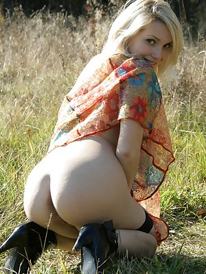 Sweet young blonde fingering pussy outdoors