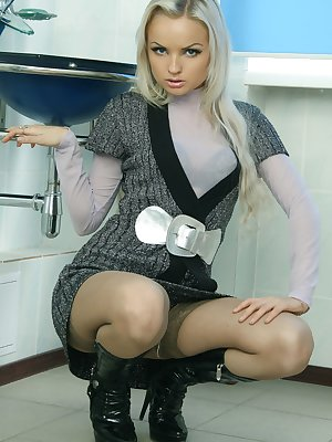 Stunning blonde shows pussy in stockings and boots