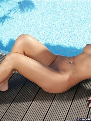 Stunning brunette getting naked by the pool