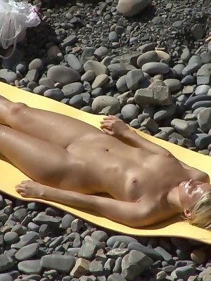 Busty blonde likes to tan her boobs