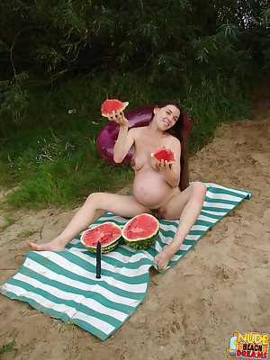 Pregnant lady poses with a watermelon then slices it in half and has a piece of it